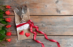 Valentines day meal setting. Valentines day cutlery set inside pouch with red roses and hearts over a wooden background Royalty Free Stock Photo