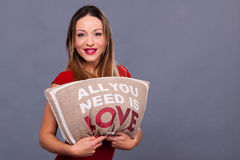 Valentines Day message with pillow all you need is love. Woman in red dress Royalty Free Stock Photo