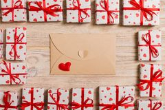 Valentines day mock up. envelope in gift boxes frame on wooden background. Valentines day card concept royalty free stock photography