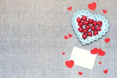 Valentines Day mockup with heart chocolate candies in plate, many paper hearts and empty card on linen fabric background. Valentine Day, love, romance, dating royalty free stock photography