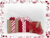 Valentines Day packages. On a white background with a border of red and pink hearts. Room for copy above the packages Stock Images