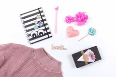 Valentines day pastel minimal flat lay. Pink sweater, notepad, pen, heart, gift, lollipop and text LOVE IS on white background.  stock image