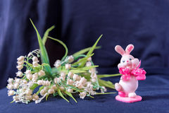 Valentines day pink bunny souvenir with lily of the valley on black background royalty free stock photography