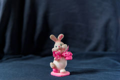 Valentines day pink bunny souvenir in the middle on black background Stock Images