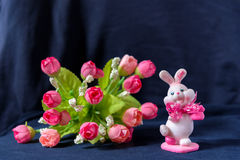Valentines day pink bunny souvenir with rose bouquet on black background Royalty Free Stock Images