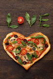Valentines day pizza in heart shape with text love on dark wooden background. Royalty Free Stock Photography