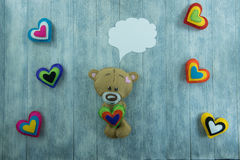 Valentines Day postcard. Teddy Bear and colourful hearts Royalty Free Stock Images