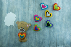 Valentines Day postcard. Teddy Bear and colourful hearts Royalty Free Stock Photos