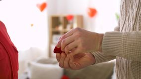 Man giving diamond ring to woman at valentines day. Valentines day, proposal and engagement concept - man giving diamond ring in little red gift box to woman at stock footage