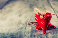 Valentines day. Red cloth handmade hearts on wooden background