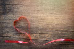 Valentines day with red ribbon heart on wooden background top view stock image
