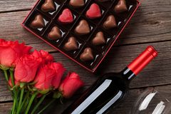 Valentines day with red roses, wine and chocolate. Valentines day with red roses, wine bottle and chocolate box on wooden table. Top view Stock Photography