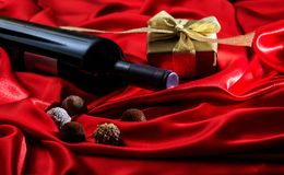 Valentines day. Red wine bottle, chocolates and a gift on red satin. Valentines day concept. Red wine bottle, chocolates and a gift box on red silk textile stock images
