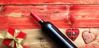 Valentines day. Red wine bottle, a gift and hearts on red wooden background. Valentines day concept. Red wine bottle, a gift box and hearts on red wooden stock photo