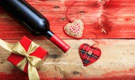 Valentines day. Red wine bottle, a gift and hearts on red wooden background. Valentines day concept. Red wine bottle, a gift box and hearts on red wooden royalty free stock images