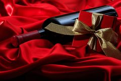 Valentines day. Red wine bottle and a gift on red satin. Valentines day concept. Red wine bottle and a gift box on red silk textile royalty free stock image