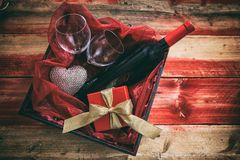 Valentines day. Red wine bottle, glasses and a gift in a box, wooden background. Valentines day concept. Red wine bottle, glasses and a gift in a box, wooden stock photo