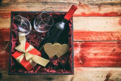 Valentines day. Red wine bottle, glasses and a gift in a box, wooden background. Valentines day concept. Red wine bottle, glasses and a gift in a box, wooden royalty free stock image