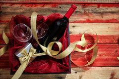 Valentines day. Red wine bottle, glasses and a gift in a box, wooden background with copyspace Royalty Free Stock Photo