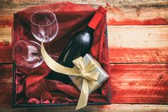 Valentines day. Red wine bottle, glasses and a gift in a box, wooden background with copyspace. Valentines day concept. Red wine bottle, glasses and a gift in a royalty free stock photos