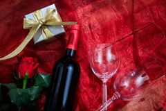 Valentines day. Red wine bottle, glasses and a gift on red textile. Valentines day concept. Red wine bottle, glasses and a gift box on red textile stock image