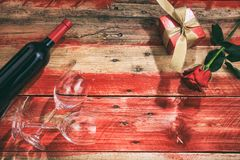 Valentines day. Red wine bottle, glasses and a gift on red wooden background. Valentines day concept. Red wine bottle, glasses and a gift on red wooden stock photography