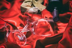 Valentines day. Red wine bottle, glasses and a gift on red satin. Valentines day concept. Red wine bottle, glasses and a gift box on red silk textile stock photo