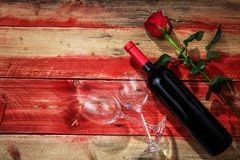 Valentines day. Red wine bottle, glasses and a rose on red wooden background. Valentines day concept. Red wine bottle, glasses and a rose on red wooden royalty free stock photography
