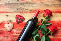 Valentines day. Red wine bottle and red roses on wooden background. Valentines day concept. Red wine bottle and red roses on wooden background stock photo