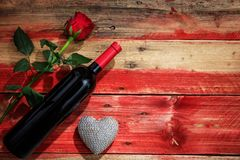 Valentines day. Red wine bottle and red rose on wooden background. Valentines day concept. Red wine bottle and red rose on wooden background royalty free stock photos