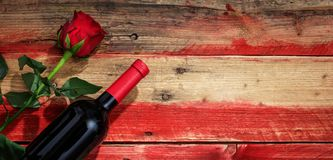 Valentines day. Red wine bottle and red rose on wooden background Stock Images