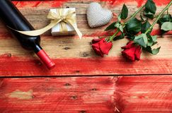 Valentines day. Red wine bottle, roses and a gift on wooden background. Valentines day concept. Red wine bottle, roses and a gift on wooden background stock photo