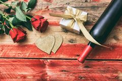 Valentines day. Red wine bottle, roses and a gift on wooden background. Valentines day concept. Red wine bottle, roses and a gift on wooden background stock images