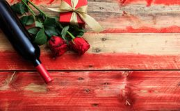 Valentines day. Red wine bottle, roses and a gift on wooden background. Valentines day concept. Red wine bottle, roses and a gift on wooden background royalty free stock photos