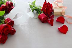 Valentines day romantic background with beautiful bouquet of roses and masquerade white mask on wooden table.