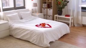 Cozy bedroom decorated for valentines day. Valentines day, romantic date and holidays concept - bed decorated with heart made of red petals and gift box in stock video footage