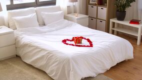 Cozy bedroom decorated for valentines day. Valentines day, romantic date and holidays concept - bed decorated with heart made of red petals and gift box in stock footage