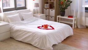 Cozy bedroom decorated for valentines day. Valentines day, romantic date and holidays concept - bed decorated with heart made of red petals and gift box in stock video