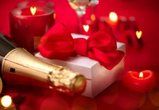 Valentines Day romantic dinner. Date. Champagne, candles and gift box over holiday red background royalty free stock photos