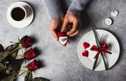 Valentines day romantic dinner table setting man hand holding engagement ring. In box marry me wedding with red rose gift surprise on grey background. Love gift Royalty Free Stock Photo