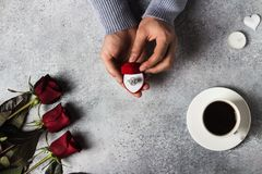 Valentines day romantic man hand holding engagement ring in box marry me. Wedding with red roses bouquet gift surprise on grey background. Love gift for woman stock photos