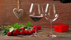 Valentines day's arrangements with red roses and two wine glasses. Over gray background stock video