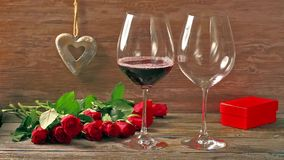 Valentines day's arrangements with red roses and two wine glasses. Over gray background stock footage