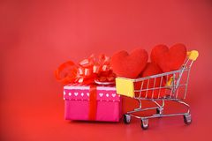 Valentines day shopping and Gift Box love concept Pink present box with ribbon bow and Red Heart in shopping cart gift box stock photography