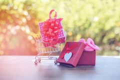 Valentines day shopping and Gift Box Shopping online Valentines day concept Pink present box with red ribbon bow on shopping cart royalty free stock photo
