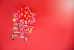 Valentines day shopping and Gift Box Pink present box with red ribbon bow on shopping cart concept Merry Christmas Holiday Happy royalty free stock image