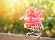 Valentines day shopping and Gift Box / Pink present box with red ribbon bow on shopping cart stock photo
