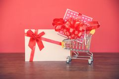 Valentines day shopping and Gift card Gift Box / Pink present box with red ribbon bow on shopping cart royalty free stock photos