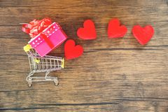 Valentines day shopping and red heart gift box on shopping cart love concept Shopping holiday for love Valentines day on wooden stock photography