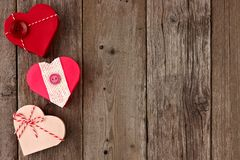 Valentines Day side border of red heart-shaped gifts over wood Royalty Free Stock Images